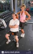 middle-aged-couple-standing-in-gym-in-workout-clothes-b74a63